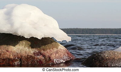 A snow melting on the rock - A snow slowly melting on top of...