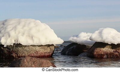 Snow on top of the big rocks are slowly meting under the...