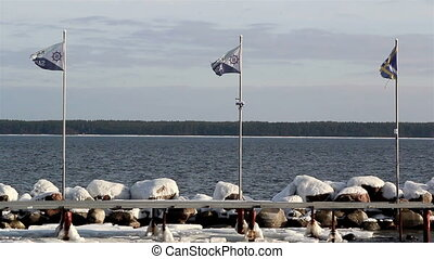 Three flags waving on the flag pole located near the shore...