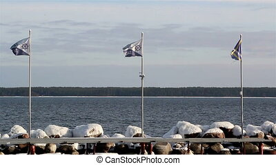 Three waving flags on the shore with the view of the nice...