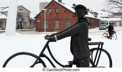 A statue of a man in bicycle and the scarf