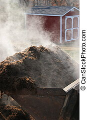 Mulch - Scoop of mulch with steam rising off it.