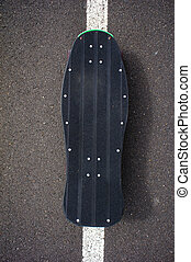 Vintage Style Longboard Black Skateboard on an Empty Asphalt...