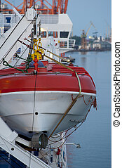 White and red lifeboat, visible ropes and elements of the...