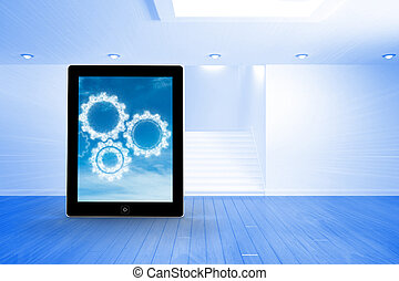 Composite image of cogs in clouds on tablet screen - Cogs in...