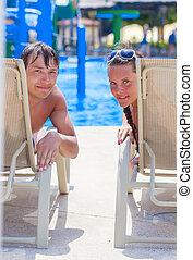 A couple is sunbathing on the beach