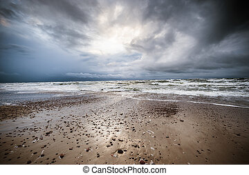 A seaview with the stormy sea, visible small stones and waves, illuminated with dramatic light and dark stormy clouds, ultra wide angle of view.