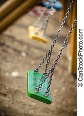 Abandoned autumn, fall playground, with green swings and...