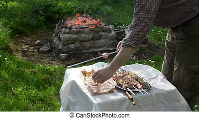 pork barbecue - a man put on a metal skewer pork barbecue