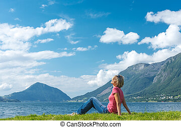 Woman relaxing enjoying at the fjord coast in a summer sunny...