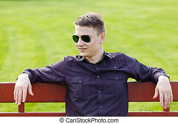Young guy waiting his girlfriend in the park