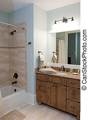 modern bathroom with wood cabinets and stone tile shower