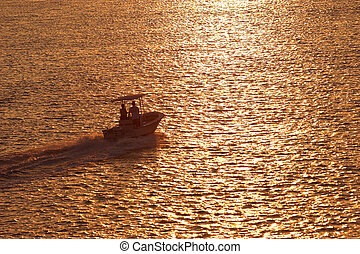 sunset boating - boat travelling across water at sunset
