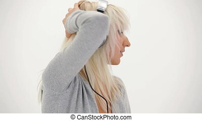 Blonde enjoying music - Blonde girl enjoying music in...