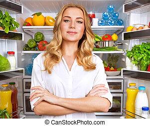 Healthy woman near open fridge - Portrait of cute serious...