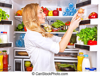 Healthy eating - Cute female taking eggs from the fridge,...