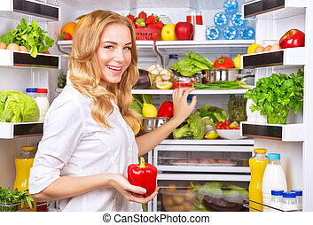 Housewife take red pepper from fridge - Housewife at the...