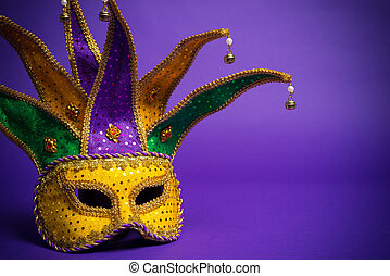 Mardi Gras or Carnivale mask on a purple background -...