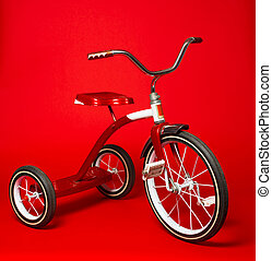 Vintage red tricycle on a bright red background - A vintage...