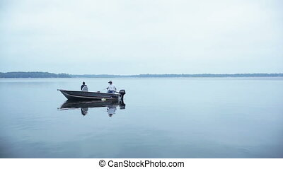 Man and woman fishing in a boat - Midaged man and woman in a...