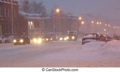 cars on a city street in a blizzard at dawn