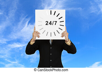 Businessman with board 24/7 on blue sky background