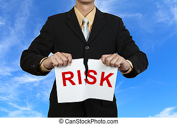 Businessman tear paper with word Risk on blue sky background