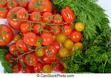 cluster of small red tomatoes with green on the white...