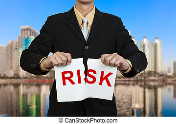Businessman tear paper with word Risk in red - Businessman...