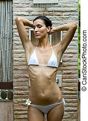 Showering Outdoors - A young slim woman showering outside