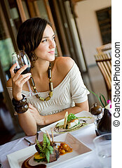 Woman In Restaurant - A young woman enjoying a meal and wine