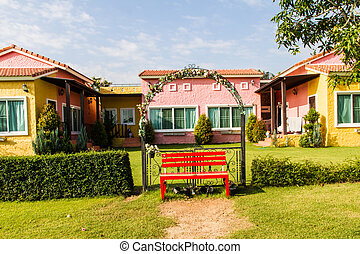 Red benches in front of colorful house