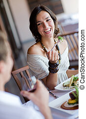 Enjoying Dinner - A young woman laughing whilst eating...