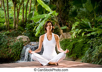 Yoga Outside - A young woman sitting outside in a yoga...