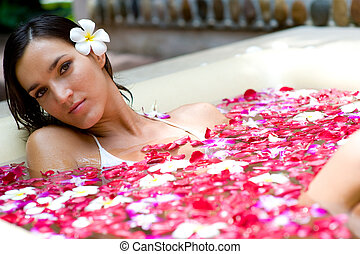 Relaxing In Bath - A young woman in a bath full of flowers
