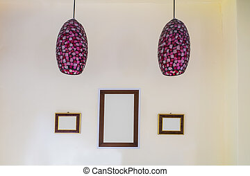 Lamps, picture frames on the white wall.