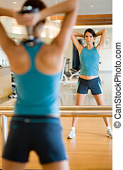 Working Out - A young attractive woman working out in gym