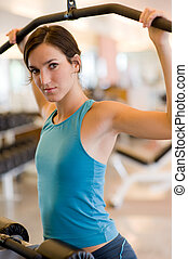 Gym Workout - A young woman working out on a machine in a...