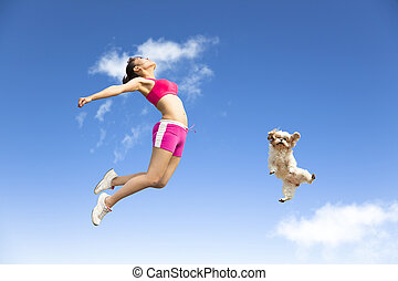 young woman and dog jumping in the sky
