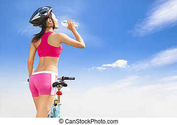 Young woman drinking water with folding bike