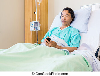 Patient Using Mobile Phone On Hospital Bed - Mature male...