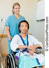 Patient Sitting On Wheelchair While Nurse Assisting Him -...