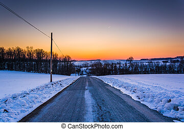 Sunset over a road through a snow-covered field in rural York County, Pennsylvania.