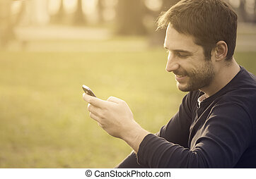 Man with smart phone - Young man sitting in the park and...