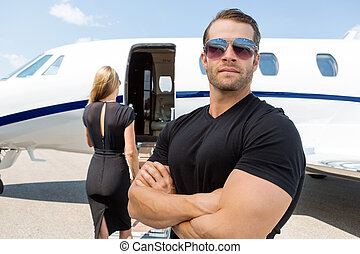 Bodyguard Standing Against Woman And Private Jet - Confident...