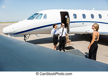 Elegant Woman Walking Towards Private Jet - Elegant woman...