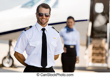 Pilot Standing With Stewardess And Private Jet At Terminal -...
