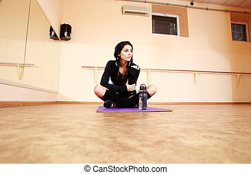 Young thoughtful fit woman sitting on the yoga mat at gym