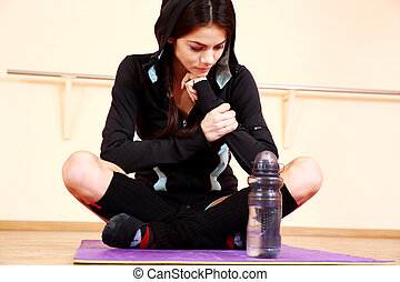 Young pensive fit woman sitting on the yoga mat at gym