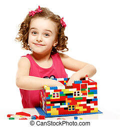 Small girl builds a house from plastic blocks